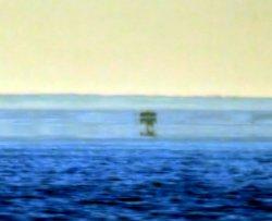В этом мираже видны как минимум три отдельных изображения лодки. Реальный в нижней и верхней части находится в вертикальном положении, тогда как один посередине перевернут.